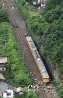脱線した電車(手前)を調べる作業員ら。奥が乗り上げたとみられる土砂=広島市安芸区で2016年6月23日午前9時5分、本社ヘリから西本勝撮影