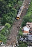 脱線した電車(奥)を調べる作業員ら。手前が乗り上げたとみられる土砂=広島市安芸区で2016年6月23日午前9時3分、本社ヘリから西本勝撮影