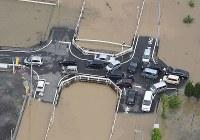 大雨の影響で冠水した道路で立ち往生する車両=広島県福山市で2016年6月23日午前8時33分、本社ヘリから西本勝撮影