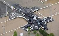 大雨の影響で冠水した道路で立ち往生する車=広島県福山市で2016年6月23日午前8時33分、本社ヘリから西本勝撮影