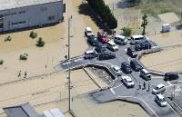 大雨の影響で道路が冠水し、立ち往生した車=広島県福山市で2016年6月23日午前10時27分、本社ヘリから西本勝撮影