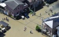 大雨の影響で冠水した道路を歩く人たち=広島県福山市で2016年6月23日午前10時27分、本社ヘリから西本勝撮影