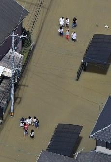 大雨の影響で冠水した道路を歩く人たち=広島県福山市で2016年6月23日午前10時28分、本社ヘリから西本勝撮影