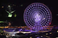 The Redhorse Osaka Wheel, right, is lit up on the night of June 23, 2016, overlooking the Tower of the Sun, left, in Suita, Osaka Prefecture. (Mainichi)