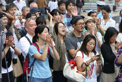 参院選が公示された22日、候補者の第一声に拍手を送る人たち=東京都新宿区のJR新宿駅前で、宮武祐希撮影