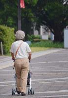 歩行器を使って歩く女性。「今日生きていくのに精いっぱい」と話す=富山市内で、大東祐紀撮影