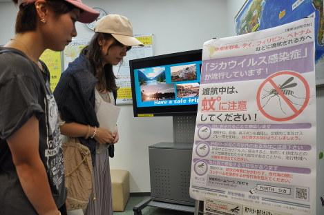 羽田空港国際線ターミナルで渡航先でのジカ熱への注意を呼び掛けるポスターに目を向ける観光客