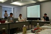 参与の塙佳憲さん(左奥)の報告を受け、議長の橋本正裕町長(右)、委員の大学教授ら(左前列)から意見が相次いだ=茨城県境町の町役場で2016年6月23日、中村美奈子撮影