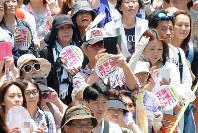 投票を訴えるうちわを手に、候補者の演説に耳を傾ける人たち=大阪市内で6月26日、加古信志撮影