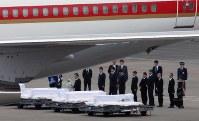 政府専用機で帰国したバングラデシュの人質テロ事件犠牲者の棺に献花する政府関係者ら=羽田空港で2016年7月5日午前6時59分、宮武祐希撮影