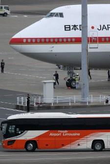 政府専用機で帰国した遺族らを乗せたと見られるバス(手前)=羽田空港で2016年7月5日午前6時10分、宮武祐希撮影