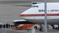 政府専用機で帰国した遺族らを乗せたと見られるバス(下)=羽田空港で2016年7月5日午前6時10分、宮武祐希撮影
