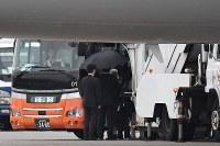 政府専用機で帰国したバングラデシュ人質テロ事件犠牲者の遺族らを空港バスに案内する人たち=羽田空港で2016年7月5日午前6時7分、三浦博之撮影