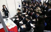 企業は即戦力を求めている。合同企業説明会で担当者から説明を聞く学生ら=大阪市で3月1日