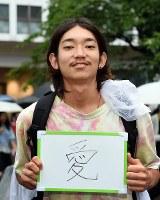 一票に「愛」という思いを託すという山本竜三さん(21)=東京都渋谷区で2016年7月9日午後2時24分、竹内紀臣撮影