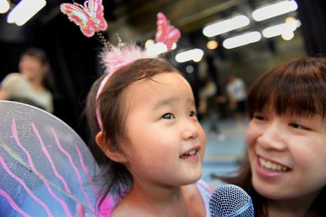 小松野さん(右)と一緒に目を輝かせて歌の練習をする愛望ちゃん=熊本市中央区で5月、和田大典撮影