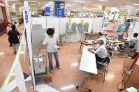 ショッピングセンターの一角に設置された高森町共通投票所で投票をする有権者=長野県高森町の「アピタ高森店」で2016年7月10日午後0時19分、徳野仁子撮影