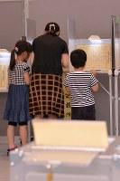 参院選で投票用紙に記入する女性=東京・千代田区役所で2016年7月10日午後3時42分、北山夏帆撮影