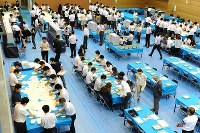 一斉に開票作業する人たち=東京都中央区で2016年7月10日午後9時1分、北山