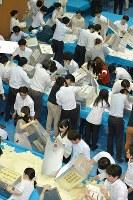 開票の合図と同時に一斉に投票箱を開ける人たち=東京都中央区で2016年7月10日午後8時50分、北山夏帆撮影