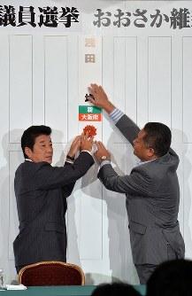 当選確実となった候補者の名前をボードに張るおおさか維新の会の松井一郎代表(左)と馬場伸幸幹事長=大阪市北区で2016年7月10日午後9時39分、加古信志撮影