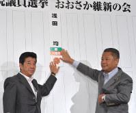 当選確実となった候補者の名前をボードに張るおおさか維新の会の松井一郎代表(左)と馬場伸幸幹事長=大阪市北区で2016年7月10日午後9時39分、平川義之撮影