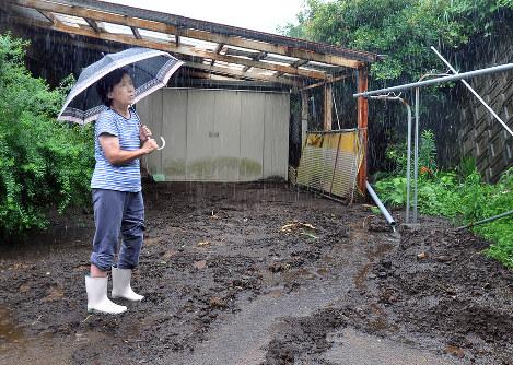 3週間ぶりに一時帰宅した自宅の敷地に流れ込んだ泥を見てため息をつく矢野さん。地震後、ホンダ熊本製作所の体育館で避難生活を続けている=熊本県南阿蘇村で3日