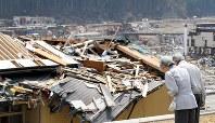 津波で被害を受けた市街地に向かって黙礼する天皇、皇后両陛下=宮城県南三陸町歌津で2011年4月27日、代表撮影