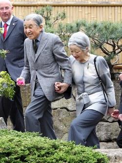 日本庭園を散策する天皇、皇后両陛下。天皇陛下の手のひらにはツバキの花がのっていた=ロンドンで2012年5月17日、尾籠章裕撮影