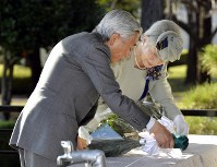 国立ハンセン病療養所「菊池恵楓園」を訪れ、献花される天皇、皇后両陛下=熊本県合志市で2013年10月26日午後2時44分、代表撮影