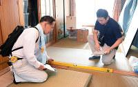 水準器を使い、床が傾いていないかを調べる空き家判定士=徳島県海陽町野江で、河村諒撮影