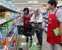 買い物おたすけ隊のボランティアといっしょに、楽々カートを押して買い物をする婦人=神戸市西区のコープデイズ神戸西で木田智佳子撮影
