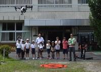 勢いよく飛行するドローン(左上)に驚く児童たち=恵那市立串原小学校で