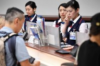 Japan Airlines employees help passengers after flights were canceled following a runway closing due to the emergency landing of a Hawaiian Airlines flight, at Haneda Airport on July 18, 2016. (Mainichi)