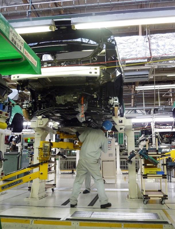 三菱自動車岡崎工場の生産ラインで、車体を組み立てる作業員ら=2014年6月、和田憲二撮影