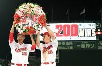 日米通算200勝を達成し、新井貴浩選手(右)から手渡された花輪を持ち記念撮影に納まる黒田博樹投手=マツダスタジアムで2016年7月23日午後9時2分、大西岳彦撮影