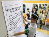 A railway worker puts up a poster warning passengers not to use their smartphones while walking at JR Shinjuku Station on July 22, 2016. (Mainichi)