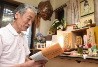Yoji Narusawa looks at a collection of poems he composed to remember his wife in front of his family's Buddhist altar at his home in Arakawa Ward, Tokyo, on June 24, 2016. (Mainichi)