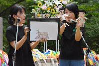 紙芝居を織り交ぜながら、自身の親の被爆体験を人形劇で表現する被爆2世の語り部たち=金沢市の卯辰山公園で、金志尚撮影