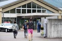 事件のあった津久井やまゆり園に入る関係者と見られる人たち=相模原市緑区で2016年7月26日午前6時54分、徳野仁子撮影