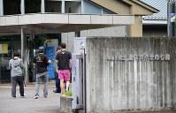 事件のあった津久井やまゆり園に入る施設関係者と見られる人たち=相模原市緑区で2016年7月26日午前6時54分、徳野仁子撮影