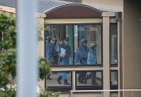 事件があった障害者施設、津久井やまゆり園を調べる警察官ら=相模原市緑区で2016年7月26日午前7時59分、長谷川直亮撮影