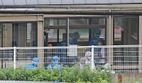 事件があった障害者施設の県立津久井やまゆり園を調べる警察官ら=相模原市緑区で2016年7月26日午前9時26分、長谷川直亮撮影
