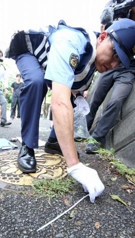 事件現場近くに落ちていた結束バンドを回収する警察官=相模原市緑区で2016年7月27日午前8時40分、宮武祐希撮影