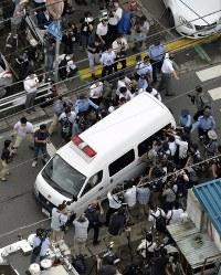 送検のため神奈川県警・津久井署を出る植松聖容疑者を乗せた車両=相模原市緑区で2016年7月27日午前7時32分、本社ヘリから