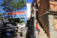 取り壊しが進む建物に座るマリアさん。横断幕には「思い出を移転することはできない」と書かれていた=リオデジャネイロで、梅村直承撮影