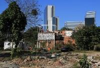 「私たちはここに住む権利がある。全てのものがお金で買えるわけではない」と書かれた横断幕が、間もなく取り壊される家に掲げられる。奥には五輪の施設が見える。ほとんどの家は無くなり、集落は五輪公園に続く道路へと姿を変えた。最後までここに住むことを訴えた20世帯は7月末に敷地内にリオ市が作った住居へ引っ越す=リオデジャネイロで、梅村直承撮影