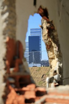 取り壊しが進む住居の穴から五輪施設が見えた=リオデジャネイロで、梅村直承撮影