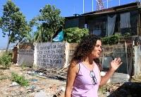奥の住居に住むサンドラ・テイシェイラさんは「跡地を高級マンションにするという計画は無くなりました。同じ場所に住むことができることになってよかった」。7月下旬に集落跡の端に作られる住居に引っ越す=リオデジャネイロで、梅村直承撮影