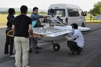 試験飛行のたびに機体を組み立てる。翼は木製の骨組みにフィルムを張った構造だ=滝川市のたきかわスカイパークで2016年7月16日午前6時44分、三股智子撮影
